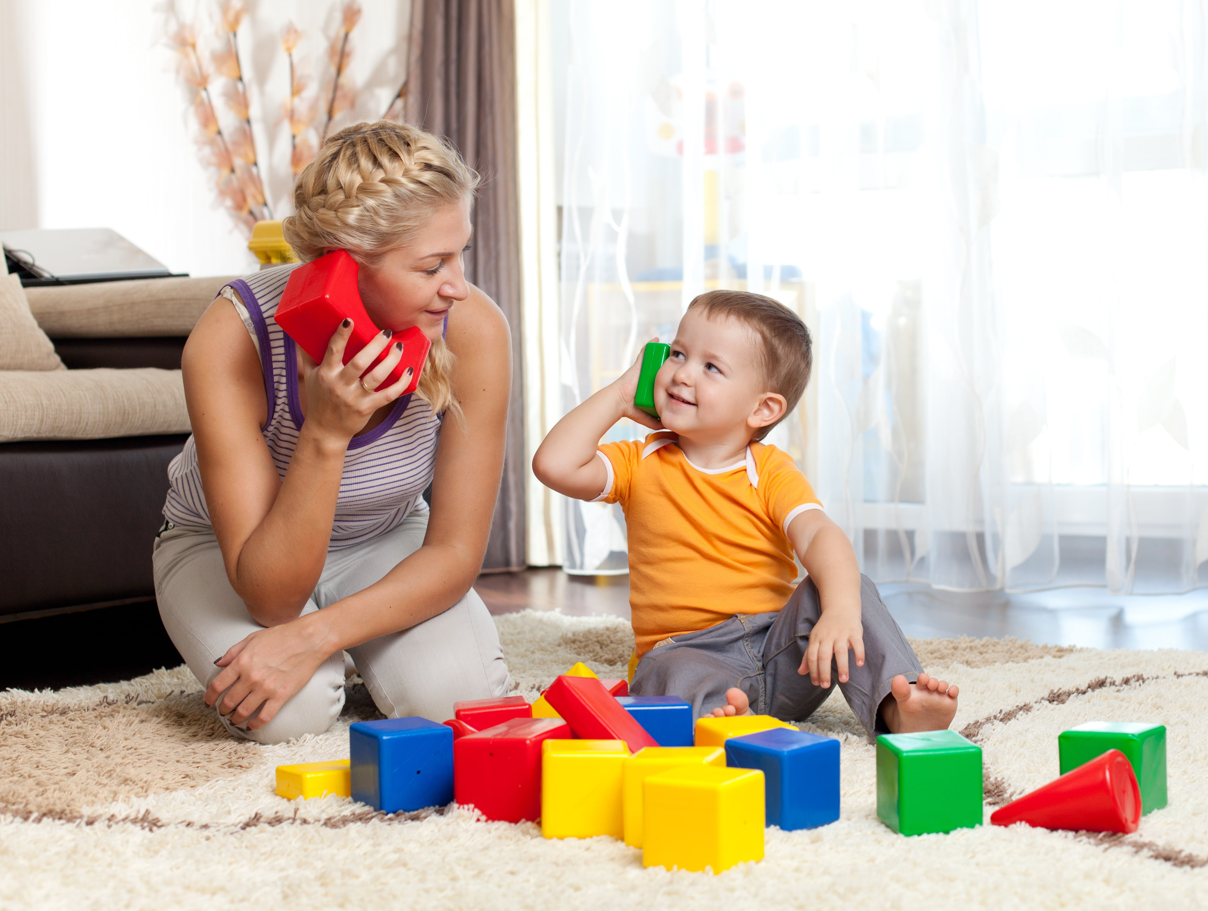 A woman and child practicing communication using toy phones and blocks; play based speech therapy